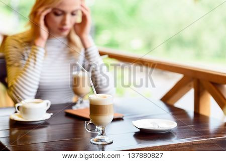 Young woman is suffering from headache. She is touching temples with frustration. Lady is sitting at table in cafeteria. Focus on glass of hot latte