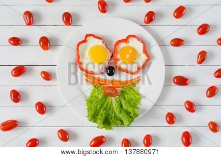 Food art, breakfast for kids. Colorful funny face on plate made with fresh healthy food. White wooden background and cherry tomatoes pattern