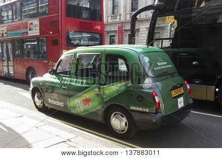 LONDON, UNITED KINGDOM - SEPTEMBER 11 2015: Heineken Branded taxi cab in the streets of London United Kingdom