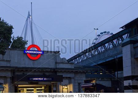 LONDON, UNITED KINGDOM - SEPTEMBER 11 2015: Embakment metro station at twilight in London with millenium wheel in the background