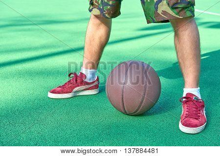 Legs stands near basketball ball on green playground