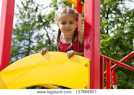 Portrait of cute little caucasian girl playing on the playground