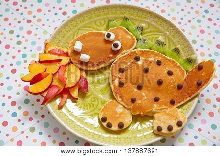 Firebreathing dragon shaped pancakes with peaches, banana and kiwi