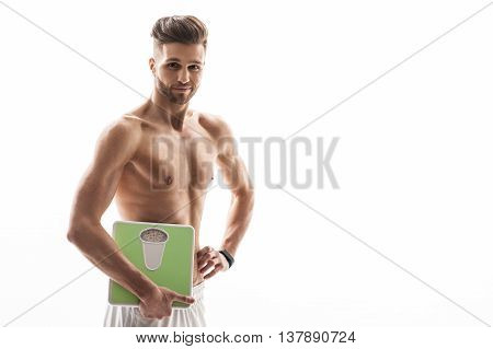 Healthy lifestyle is the best diet. Fit young man is holding balance near his body. He is standing and smiling with proud. Isolated and copy space in right side
