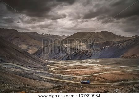Chinese truck struggling and moving slowly on the stunningly beautiful mountain road through the Western Tibet, China