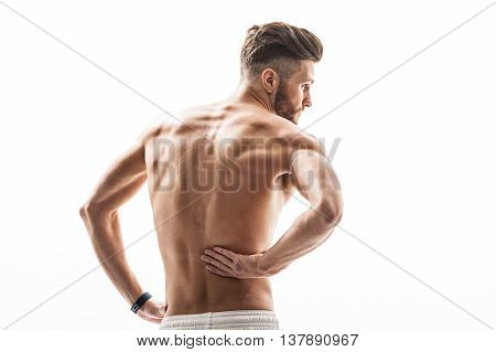 Fit man suffers from pain. He is touching his back with desperation. Isolated
