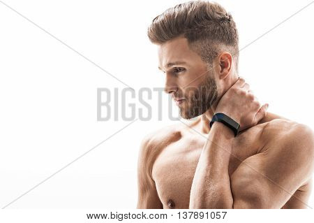 Young sporty man feels pain in neck. He is massaging in pensively. Sportsman is standing with naked torso and looking forward pensively. Isolated and copy space in left side