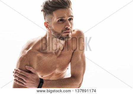Fit man is suffering from ache in arm. He is touching it and looking forward with desperation. Isolated and copy space in right side