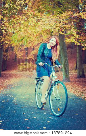 Nature outdoors concept. Young girl on the way to autumn. Pretty woman is riding the bicycle. Lady is wearing blue dress and leather jacket.