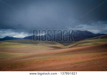 Snow falling on the mountain slopes in the landscape of the remote area of Western Tibet