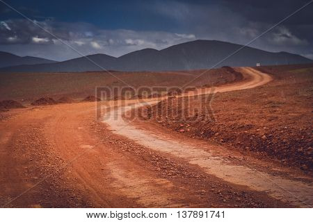 Snow falling in summer on a muddy and clay mountain road through the high central Tibetan plateau, Tibet, China