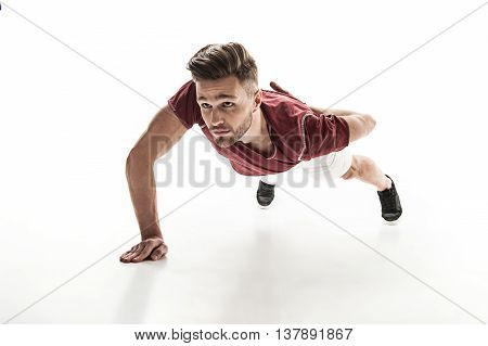 Attractive young man is doing push ups with concentration. He is leaning his body on one arm. Isolated