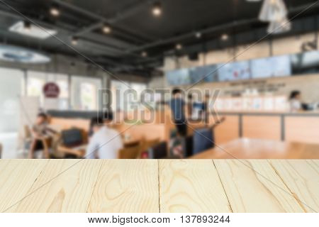 Wooden table top on blur background of coffee shop for display your product.