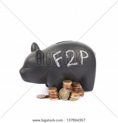 Word F2P written with chalk on a black ceramic piggy bank coin container next to a pile of euro coins, composition isolated over the white background