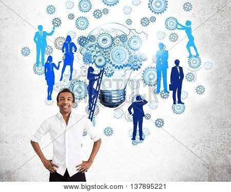 Teamwork concept with confident african american businessman and abstract drawing of gears lightbulb and people silhouettes on ladder. Concrete wall background