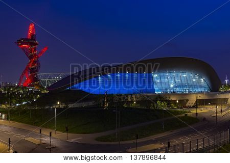 London England - May 27 2016: Night view of the illuminated London Aquatics Centre Olympic stadium and ArcelorMittal Orbit observation tower in the Olympic Park of London England.