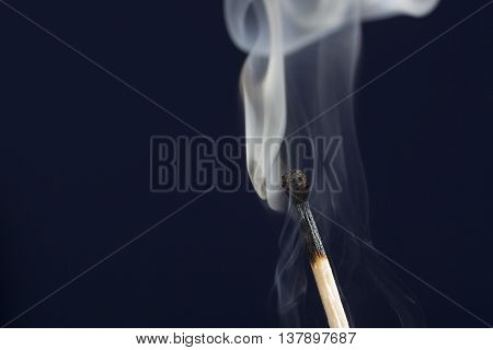 Extinguished match close up with smoke on dark blue background