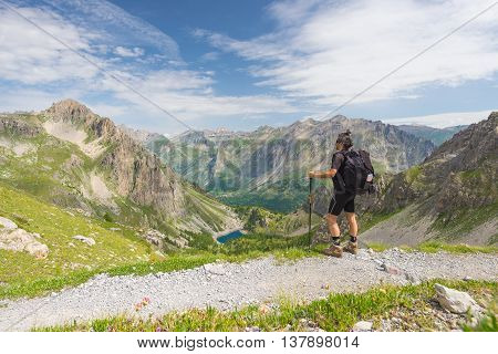Backpacker Hiking On Footpath And Looking At Expansive View From The Top. Summer Adventures And Expl
