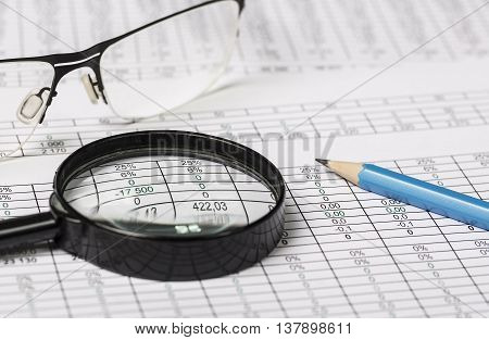 Business research. Closeup of spectacles, magnifying glass and pencil on paper with digits and tables
