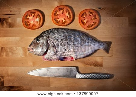 Delicious fresh sea bream fish on wooden kitchen board with tomatos