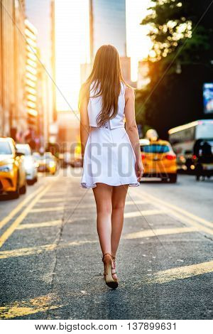 Beautiful girl wearing white mini dress and walking on New York City street. Female summer outfit street fashion concept. Woman making step on traffic lane in city at sunset time.