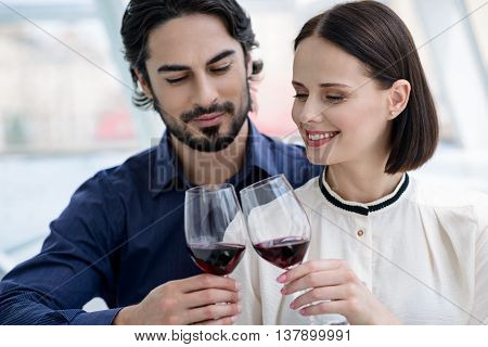 Happy loving couple is celebrating anniversary. They are clinking glasses of wine and smiling