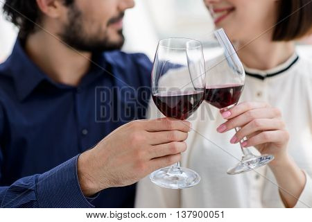 Cheers. Joyful married couple clinking wineglasses and smiling. Man is sitting and embracing woman. Focus on glasses of wine