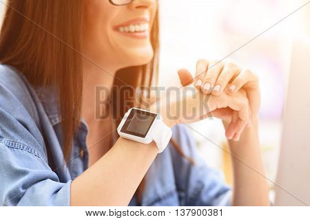 Time for meeting with friend. Cropped view of young woman wearing smartwatch and smiling