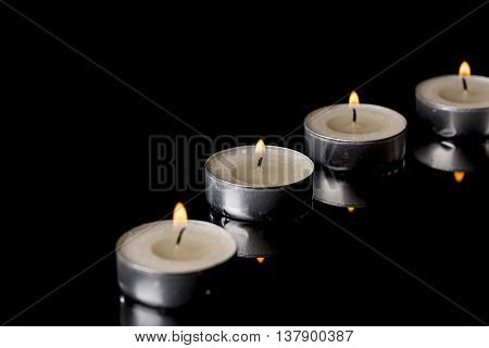 Lit Tea Candles with Reflection on Black background
