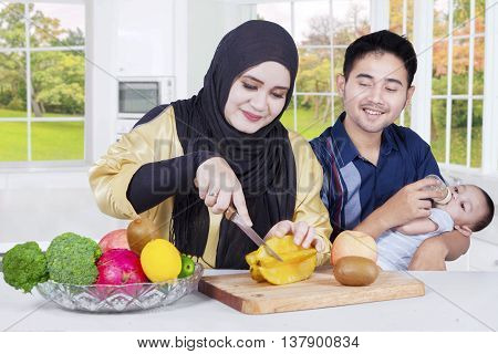 Happy arabian family with their baby cooking together in the kitchen with autumn background on the window