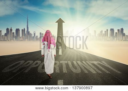 Back view of Arabian young businessman walking on the highway with Opportunity word and turning into upward arrow