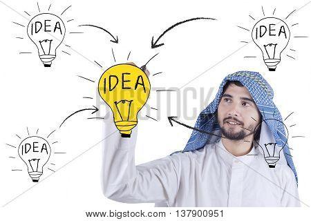 Portrait of Arabian businessman drawing idea scheme with lightbulb on the whiteboard