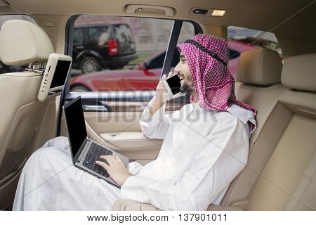 Portrait of Arabian businessman talking on the cellphone while using laptop computer in the car