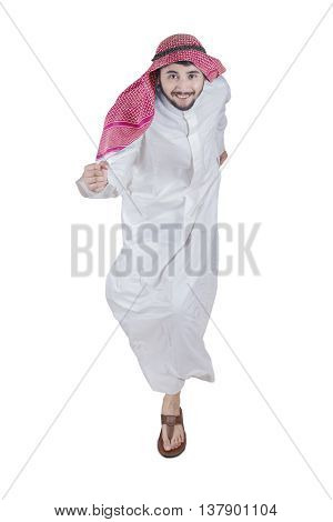 Portrait of Arabic businessman wearing islamic clothes and running in the studio while smiling at the camera