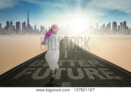 Arabic businessman running on the road with text of Better future and bright sunlight