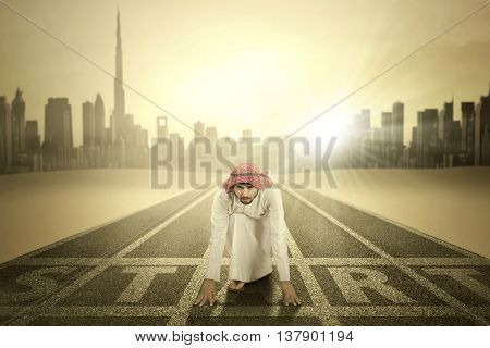 Arabic young businessman takes ready poses on the start line and ready to race shot on the road