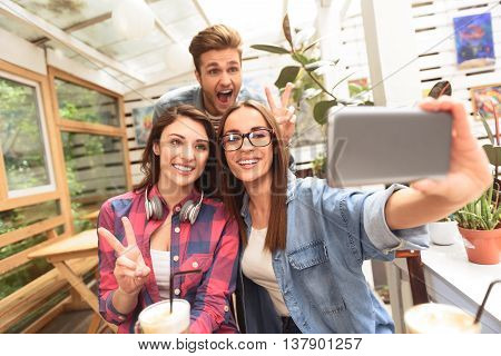 Fun times make best memories. Shot of group of friends taking selfie together with cellphone in coffee shop