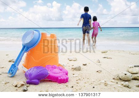Image of children's beach toys two children playing on the tropical beach