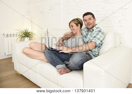 young attractive 30s couple in love sitting on couch together with laptop computer happy at home living room using the internet smiling cheerful and satisfied in technology and lifestyle concept