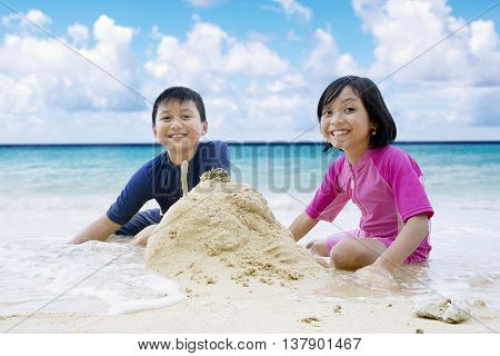 Portrait of two cheerful children sitting on the beach while making sandcastle and smiling at the camera