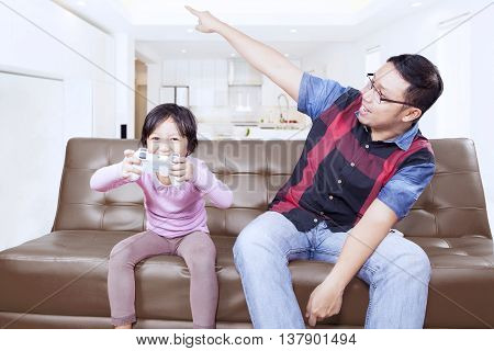 Portrait of a little girl enjoy playing video game while father scolding her at home