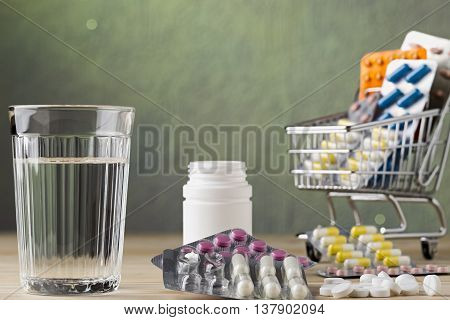 Set of glass water and pill blister packs on wooden table