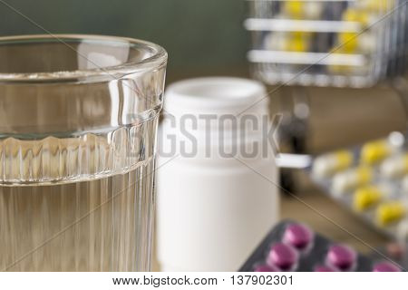 Glass of clean water and pill blister packs on wooden table