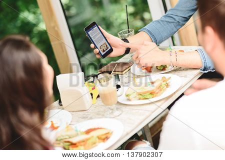 This article about us. Close up of man showing to his friends last news on Internet, pointing finger at screen of smartphone