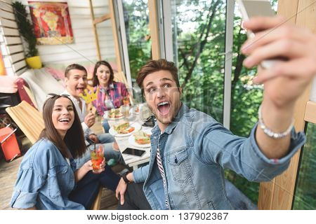 That great combination of friends and good food. Top view of group of friends enjoying lunch together and making selfie
