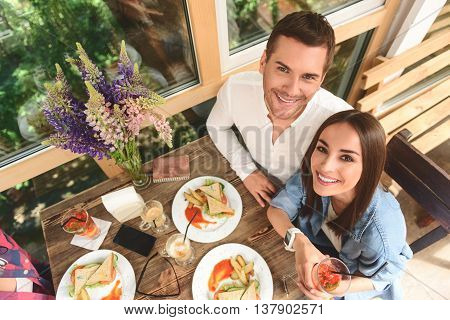 Important to be together. Top view of cute man and woman sitting in coffee shop during lunch, looking at camera and smiling happily