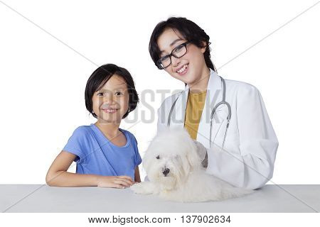 Portrait of cute little girl and young veterinarian smiling at camera with maltese dog on the desk