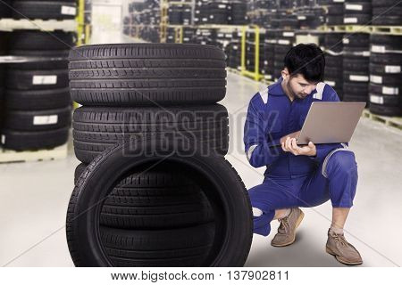 Portrait of young mechanic wearing blue uniform and using a laptop to check tires at workshop