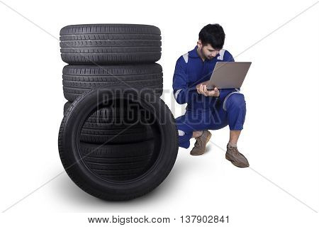 Arabian mechanic working with laptop computer next to a pile of tires isolated on white background