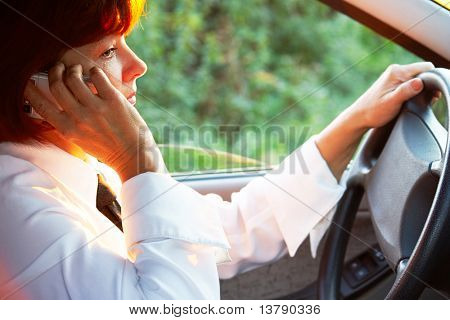 Photo of middle aged female talking by the phone with serious expression in car